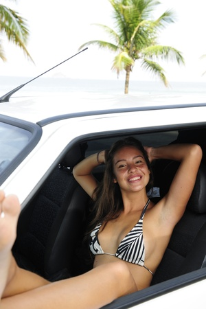 car rental: woman relaxing in her car near the beach photo