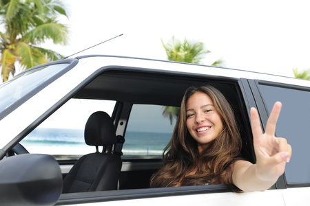 car rental: happy woman in her car near the beach showing victory sign photo