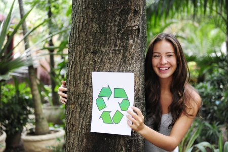 recycling: woman in the forest holding a recycle sign smiling