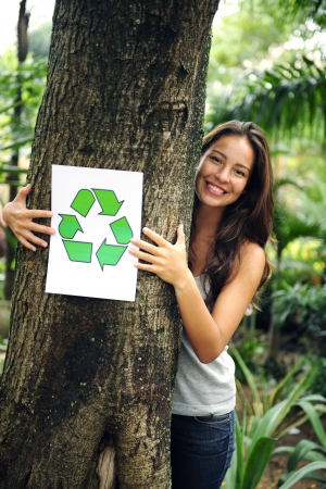 environmental concept: recycling: woman in the forest holding a recycle sign smiling