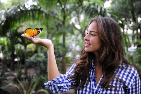 activist: biodiversity: butterfly sitting on the hand of a young woman in the forest