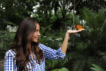 biodiversity: butterfly sitting on the hand of a young woman in the forest photo