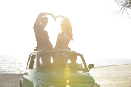 roadtrip: romantic vacation: couple at sundown on the beach with car Stock Photo