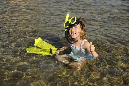 Happy cute snorkel girl on vacation in the water photo