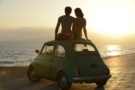 trip: romantic vacation: couple at sundown on the beach with car Stock Photo