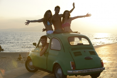Vacation: Group of happy friends with small car on the beach