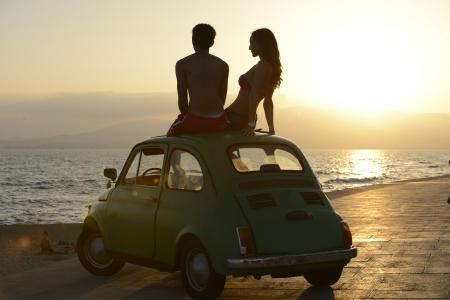 persona viajando: rom�ntico Alquiler de vacaciones: Pareja al atardecer en la playa con coche Foto de archivo