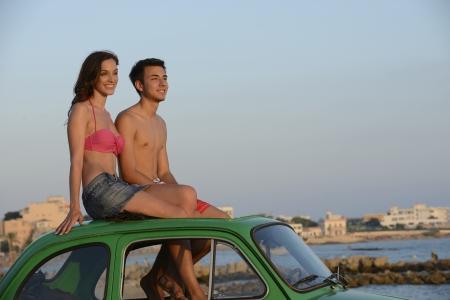cabrio: gelukkig jong koppel met een kleine auto op vakantie Stockfoto