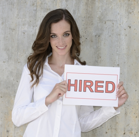 recruitment : happy woman holding a hired sign photo