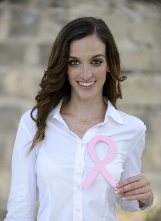 breast examination: woman holding pink breast cancer support ribbon