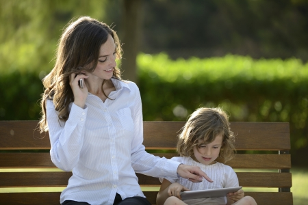 Mother on phone with daughter using digital tablet in the park photo