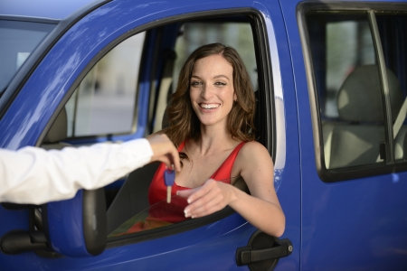 auto leasing: happy woman receiving keys of her new car