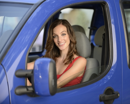 happy woman driving her new blue car Stock Photo