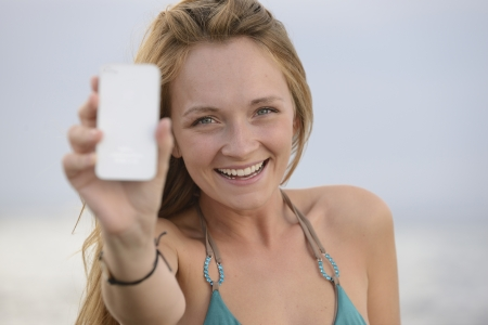 blond woman with cellphone on the beach photo