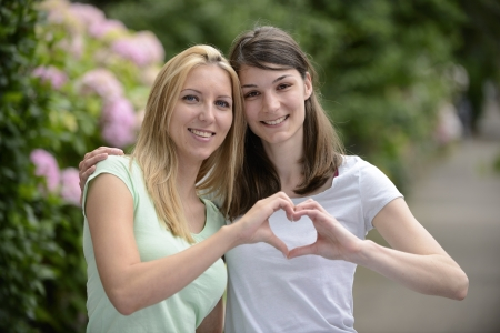 homosexual couple: lesbian couple forming heart shape with hands