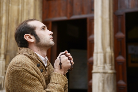 Man or monk praying in front of the church with rosario or prayer beads Stock Photo - 17055187
