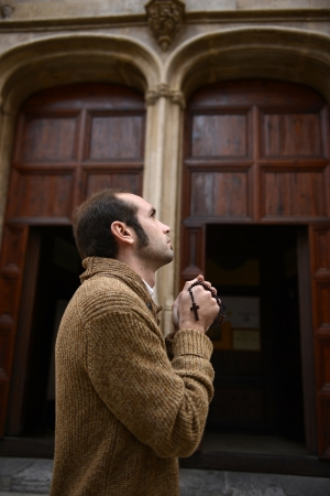 Man or monk praying in front of the church with rosa or prayer beads Stock Photo - 17055182