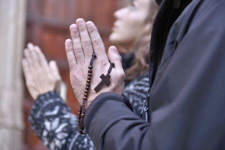 Hands of a praying couple holding prayer beads in church photo