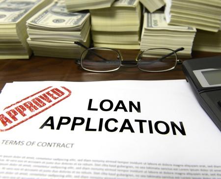 tomar prestado: Aprobado pr�stamo impreso de solicitud y las pilas de billetes de 100 d�lares