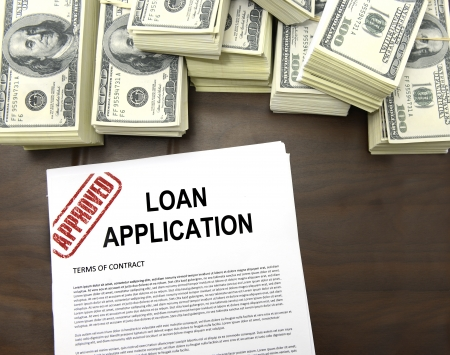 Approved loan application form and stacks of 100 dollar bills photo