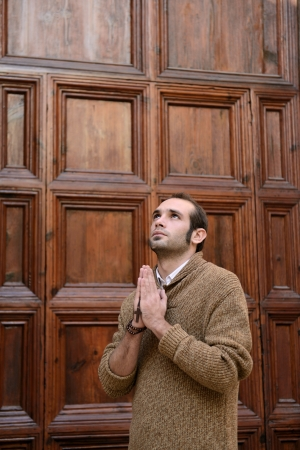 Man or monk praying in front of the church with rosario or prayer beads Stock Photo - 17055191