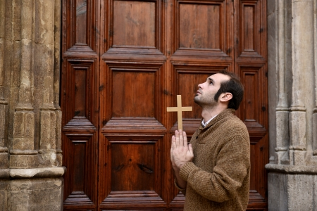 Man or monk praying in front of the church holding a cross Stock Photo - 17055193