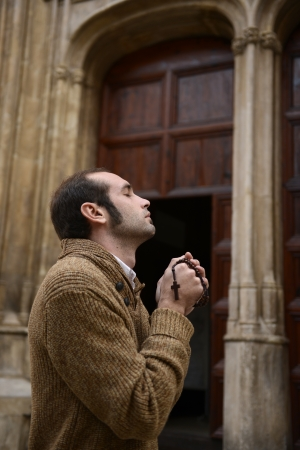 Man or monk praying in front of the church with rosario or prayer beads Stock Photo - 17055181
