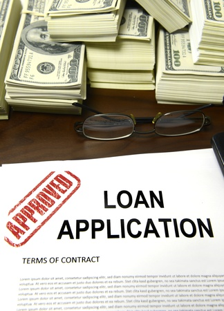 Approved loan application and dollar bills on desk photo