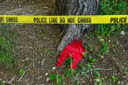 Crime scene: Police line do not cross tape and romper suit as evidence photo