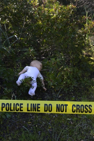 Crime scene in the forest: Yellow police line do not cross tape and doll photo