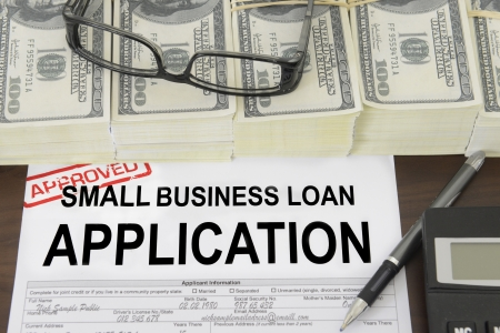Approved small business loan application form and dollar bills photo