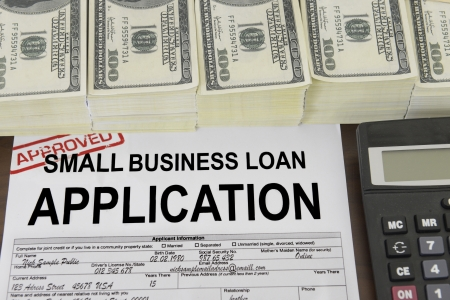 approved: Approved small business loan application form and dollar bills