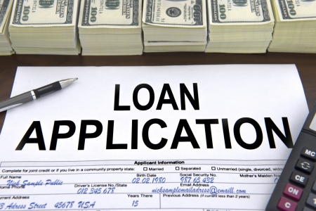 lending: Approved loan application form and stacks of 100 dollar bills