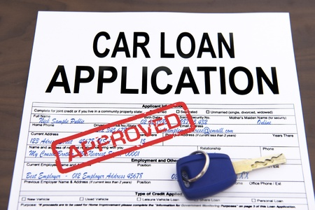 car loans: Approved car loan application form and key on desktop