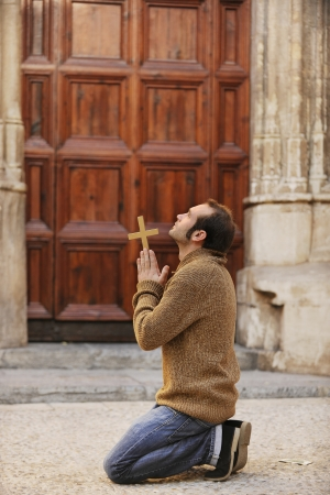 Man or monk praying in front of the church holding a cross photo