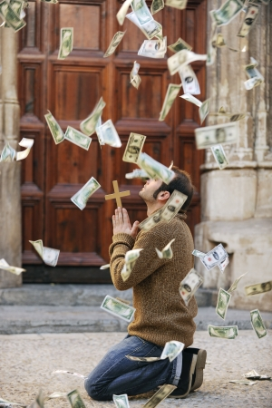 God is answering prayer: Man praying and money falling from the sky photo