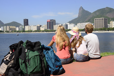 Group of backpackers tourists friends sitting on the edge of Guanabara bay watching the Christ the Redeemer.