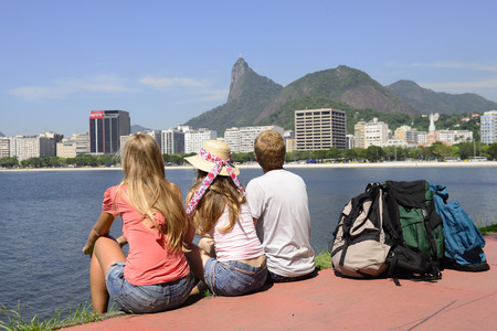 Group of tourists friends sitting on the edge of Guanabara Bay watching the Christ the Redeemer. photo