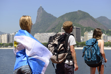 Argentinian backpackers and sport fans walking through Rio de Janeiro with Christ the Redeemer in background. photo