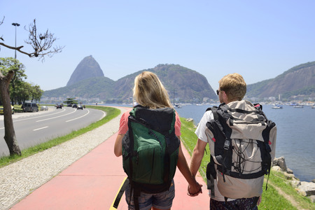 Couple of tourists backpackers walking through Rio de Janeiro with Sugar Loaf in the background. photo