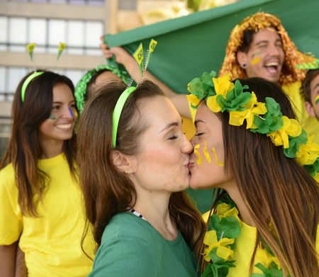 Cheerful couple of Brazilian girlfriends soccer fans kissing each other celebrating victory. photo