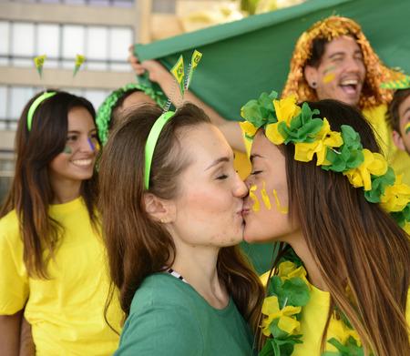 Pareja alegre de los fans novias de f�tbol brasile�os se besan victoria celebrando. photo