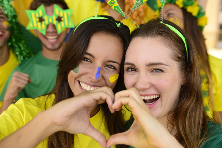 Cheerful couple of Australian or Brazilian or Cameroonian girlfriends soccer fans. photo