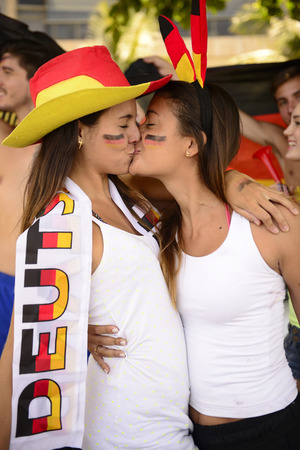 Couple of German lesbian sport soccer fans kissing each other celebrating. photo