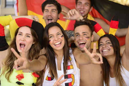 german: Group of enthusiastic German sport soccer fans celebrating victory.