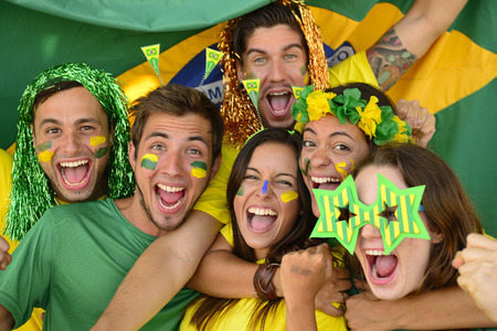 cheering fans: Happy group of Brazilian sport soccer fans amazed celebrating victory together. Stock Photo