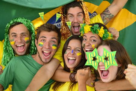 soccer fans: Happy group of Brazilian sport soccer fans amazed celebrating victory together. Stock Photo
