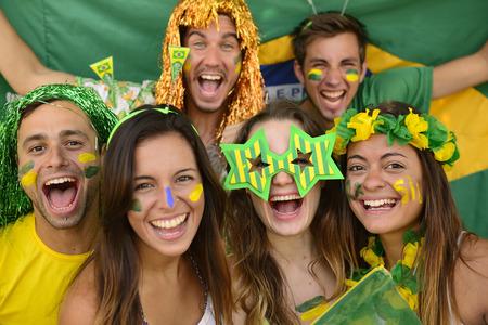 Happy group of Brazilian sport soccer fans amazed celebrating\ victory together.