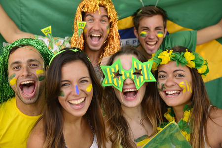 Happy group of Brazilian sport soccer fans amazed celebrating victory together. Stock Photo