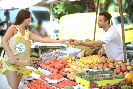 health fair: Small business owner at an open street market, handing out a fruit to a consumer carrying a shopping paper bag with a 100% organic certified label full of fruit and vegetables.